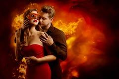 Varm flammande kyss för par, förälskad kyssa kvinna för man i röd maskering för fantasi royaltyfri foto