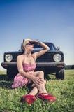 Varm flicka som poserar bredvid den retro bilen Fotografering för Bildbyråer