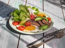 Varm frukost av stekt lever och förvanskade ägg, dobvki av grönsallat och körsbärsröda tomater på ett lantligt brädemagasin arkivfoto