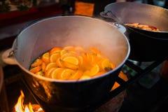 Varm gluhwein eller funderat vin i en kittel på mässan, lokal fest, varmt och kryddigt En varm hälsosam traditionell citrus drink royaltyfria foton