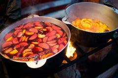 Varm gluhwein eller funderat vin i en kittel på mässan, lokal fest, varmt och kryddigt En varm hälsosam traditionell citrus drink arkivbilder
