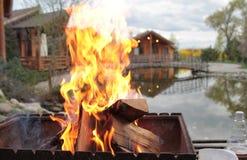 Varm grillfestbrand på gammal husbakgrund med halmtäcker taket i vinternatt Arkivfoton