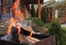 Varm grillfestbrand på gammal husbakgrund med halmtäcker taket i vinternatt Arkivbilder