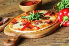 Varm hemlagad pizza med peperonin, paprica, rucola på trätabellen Arkivfoton