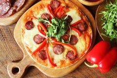 Varm hemlagad pizza med peperonin, paprica, rucola på trätabellen Top beskådar Royaltyfri Foto