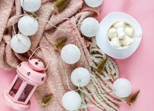 Varm hemtrevlig vinterhalsduk, lightbox på pastell och kopp kaffe med marshmallowrosa färgbakgrund nytt år för jul fotografering för bildbyråer