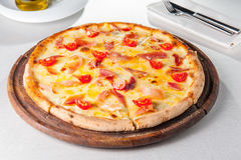 Varm köttpizza för selektiv fokus med hamon, ost och körsbärsröda tomater på träbrädet på den tjänade som restaurangtabellen Royaltyfria Bilder
