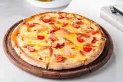 varm köttpizza med hamon, ost och körsbärsröda tomater på träbrädet på den tjänade som restaurangtabellen Fotografering för Bildbyråer