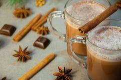 Varm kaffe eller choklad för juldrinkkakao med mjölkar i en liten kopp Granträdfilial, muttrar, stjärnaanis för kanelbruna pinnar Arkivfoto