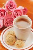 Varm kaffe, kaka och rosa färgblomma Royaltyfri Bild