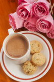 Varm kaffe, kaka och rosa färgblomma Fotografering för Bildbyråer