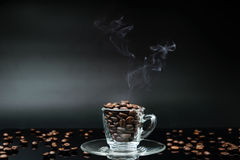 Varm kaffeböna i kaffekopp royaltyfria bilder