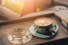 Varm kaffeexponeringsglaskopp på trätabellen i coffee shop med grön naturlig bakgrund royaltyfria bilder