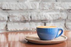 Varm kaffekopp med mot vita lodisar för tegelstenvägg fotografering för bildbyråer