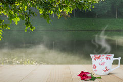 Varm kaffekopp och röd blomma på trätabellöverkant på suddig dimmig sjö- och skogbakgrund Royaltyfri Bild