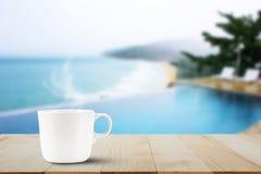 Varm kaffekopp på trätabellöverkant på suddig pöl- och strandbakgrund Royaltyfri Bild