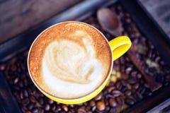 Varm kaffemocka och kaffebönor på trätabellen Royaltyfri Foto