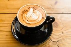 Varm kaffemocka på den bruna trätabellen med choklad Arkivbild