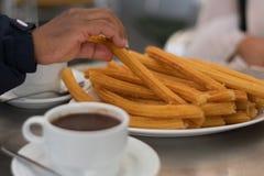Varm kopp av choklad med artisenalchurros arkivfoton