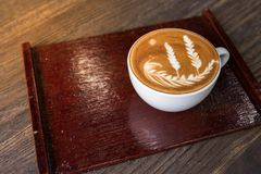 Varm kopp för kaffelattekonst med plattan royaltyfri foto