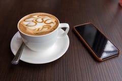 Varm kopp för lattekonstkaffe med den smarta telefonen royaltyfri fotografi