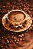 Varm kopp kaffe som omges med kaffebönor Arkivbild