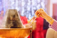 Varm kruka för varm kruka med en hand med pinnar royaltyfri fotografi