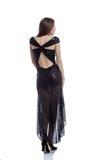 Varm kvinna i den eleganta klänningen som tillbaka poserar till kameran Arkivbilder