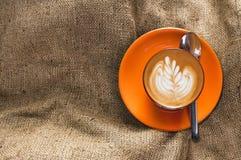 Varm latte för bästa sikt i orange kopp med den blom- modellen i skum på säckvävbakgrund Arkivbilder