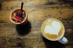 Varm latte i en vit rånar och en kruka av kulöra blyertspennor Royaltyfri Bild