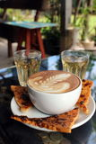 Varm Latte i trädgården med sött russinrostat bröd Royaltyfri Foto