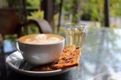 Varm Latte i trädgården med sött russinrostat bröd Fotografering för Bildbyråer