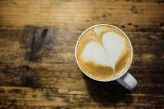 Varm latte med konst för hjärtaformlatte i en vit rånar på träta Arkivfoton