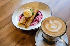 Varm latte med lattekonst av tulpanblomman med bakgrunden av blåbärkräppar Arkivfoto