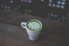 Varm lattekonst för grönt te på trätabellen Royaltyfri Bild