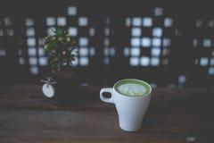 Varm lattekonst för grönt te på trätabellen Arkivbilder