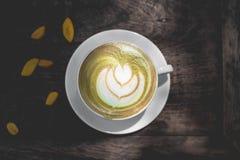 Varm lattekonst för grönt te på trätabellen Arkivbild