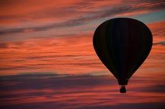 Varm-luft ballongflygande bland rosa färg- och apelsinmoln Royaltyfri Fotografi