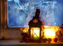 Varm lykta på det djupfrysta fönstret, vintermagi Arkivbild