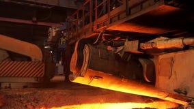 Varm metallproduktion på fabriken, metallurgibegrepp Materiellängd i fot räknat Smält stål som flödar i metallurgical bana arkivfilmer