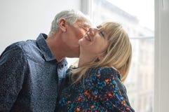 Varm och sexig medel?lders kvinna som tycker om kramen av hennes ?ldre make som st?r n?ra ?ppnad f?nsterinsida deras hem Par royaltyfri fotografi