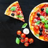 Varm pizza med Mozzarellaost och tomater som tjänas som om en blac Royaltyfria Foton