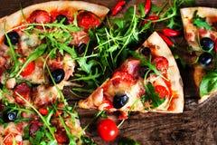Varm pizzaskiva med peperonin, smältande ost på en lantlig woode fotografering för bildbyråer