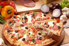 Varm pizzaskiva med sm?ltande ost p? en lantlig tr?tabell fotografering för bildbyråer