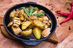 Varm portion panna med höna och potatisar Arkivbild