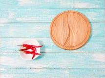 Varm röd peppar på den vita plattan, pizzaskrivbord på den gamla blåa tabellen, kopieringsutrymme royaltyfria bilder