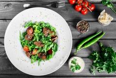 Varm sallad med stekt lever, körsbärsröda tomater och blandade gräsplaner på mörk träbakgrund sund mat royaltyfri fotografi
