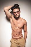 Varm sexig benägenhet för ung man på en wal vit Fotografering för Bildbyråer
