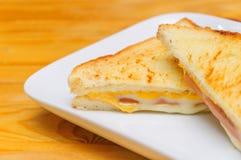 Varm smörgås med skinkaost med wood bakgrund Arkivbild