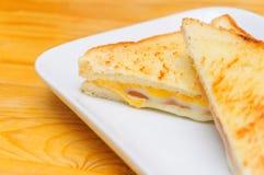 Varm smörgås med skinkaost på dishen med wood bakgrund Royaltyfri Foto